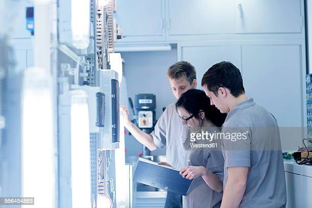 Students at electronics vocational school looking in folder