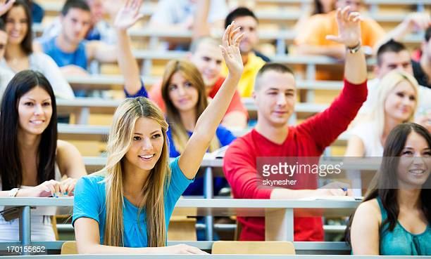 Students at lecture hall with raised hands.