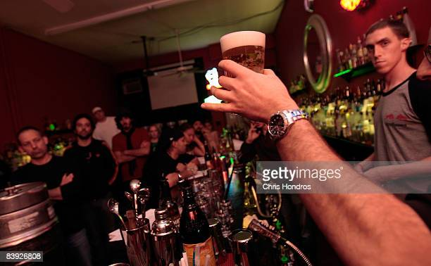 Students at the New York Bartending School watch instructor Max Shulman hold up a perfectly poured glass of beer December 5 2008 in New York City...