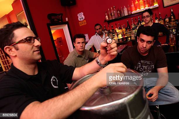 Students at the New York Bartending School watch instuctor Max Shulman demonstrate how to tap a beer keg December 5 2008 in New York City Enrollment...