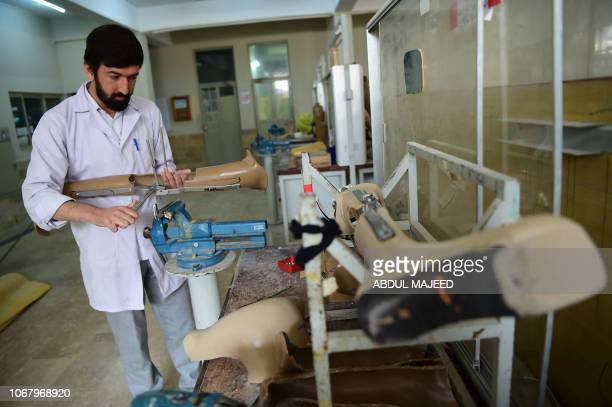 Students at the Pakistan Institute of Prosthetic and Orthotic Sciences prepare prosthetics in Peshawar on December 3 on the International Day of...