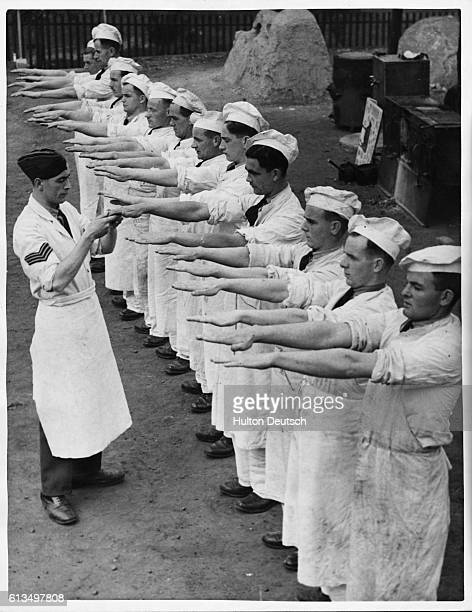 Students at the Royal Air Force School of Cookery wait to have their hands examined by their instructor before the day's cooking commences