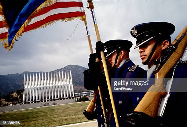 Students at the United States Air Force Academy perform duties as the Color Guard during daily noontime ceremonies on the campus In the background is...