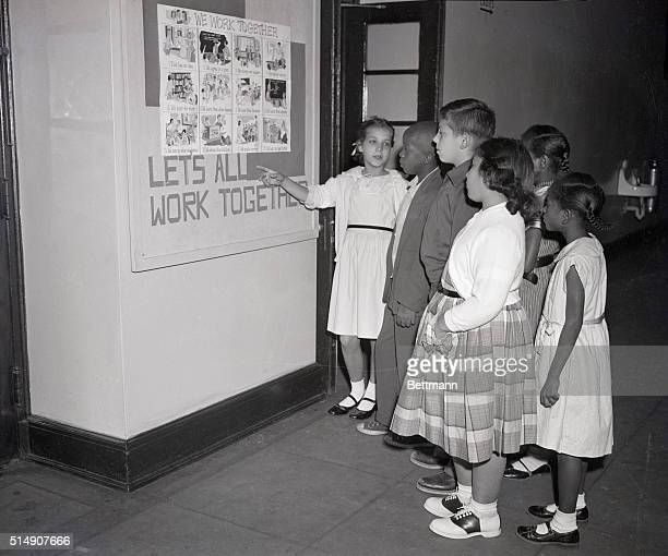 Students at Thompson Elementary School in Washington DC, formerly for white children only, study a poster urging all to work together during...