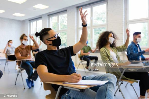 students at university during coronavirus pandemic - hand raised stock pictures, royalty-free photos & images