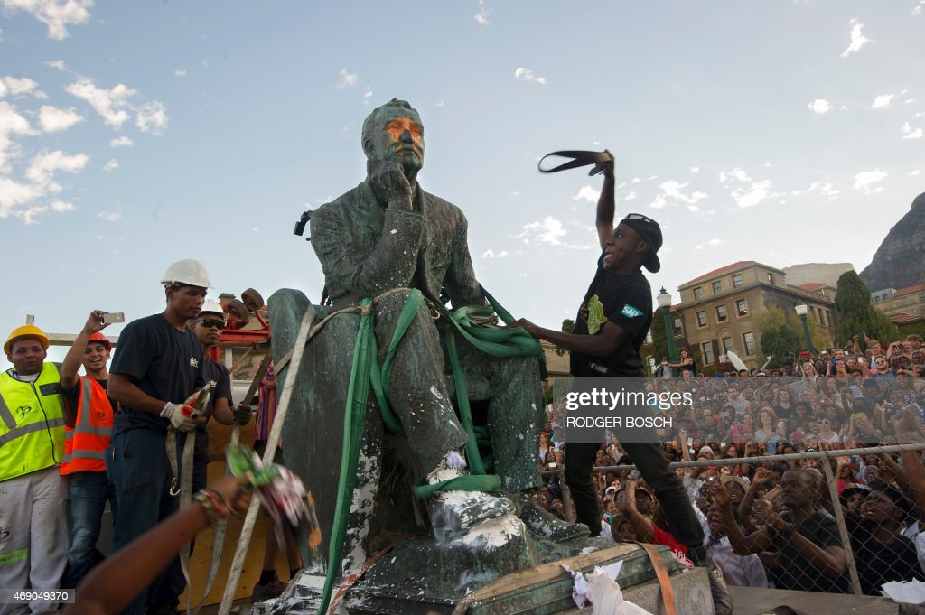 Students attack the defaced statue of British mining magnate and politician, Cecil John Rhodes, as it is removed by a crane from its position at the University of Cape Town on April 9, 2015, in Cape Town. Black students celebrated the fall of a statue of the British colonialist at the university as some white groups protested what they see as threats to their heritage. Cheers went up as a crane removed the huge bronze statue from its plinth at South Africa's oldest university after a month of student demonstrations against a perceived symbol of historical white oppression.