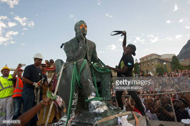 Students attack the defaced statue of British mining magnate and politician Cecil John Rhodes as it is removed by a crane from its position at the...