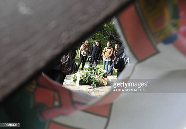 Students attend a commemoration ceremony dedicated to the 1956 uprising against Soviet occupation, near the grave of Hungarian former Prime Minister...