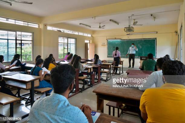 Students attend their class at a college as the state government education department directed the reopening of degree colleges after several months...