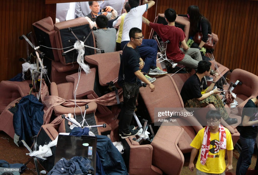 Students block the entrace of the main chamber at the Taiwanese Parliament to prevent the police from coming in on March 19, 2014 in Taipei, Taiwan. Over 200 students broke into the Taiwan Parliament and took over the main chamber in protest against the service and trade aggreement.