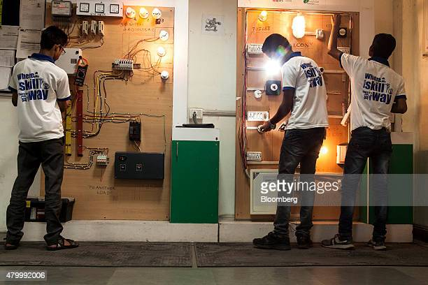 Students carry out electrical circuit tests in an electronics class during vocational training class at the Infrastructure Leasing Financial Services...