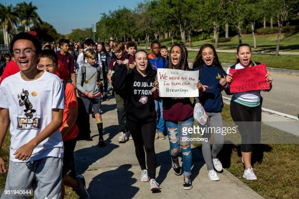 Students carry signs and chant while walking outside Marjory Stoneman Douglas High School during the ENOUGH National School Walkout rally in Parkland...