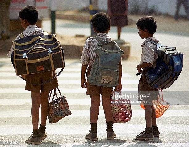Students carrying school bags wait for a break in the traffic flow to cross a busy street in Bangalore 19 February 2001 According to a recent study...