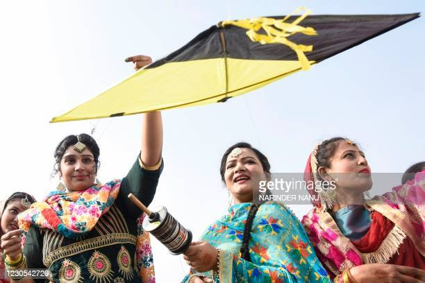 Students clad in traditional Punjabi dresses fly kites on the eve of the Lohri festival in Amritsar on January 12, 2021.