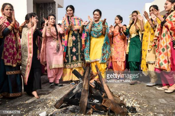 Students clad in traditional Punjabi dresses perform the giddha folk dance around a bonfire on the eve of the Lohri festival in Amritsar on January...