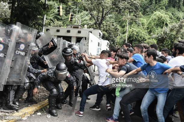 Students clashing with riot police during the demonstration. Tension rose in Venezuela after university students protested in the streets in support...