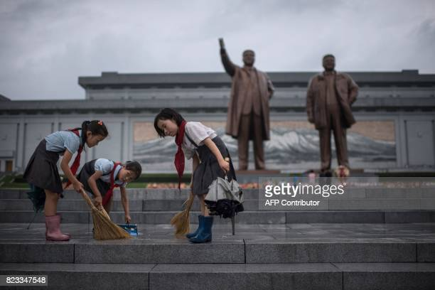 Students clean the steps in front of the statues of late North Korean leaders Kim IlSung and Kim JongIl at Mansu hill as the country marks 'Victory...