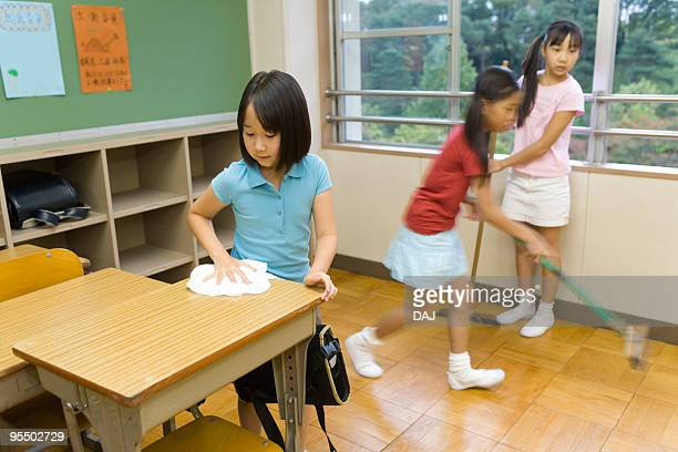 Students cleaning classroom