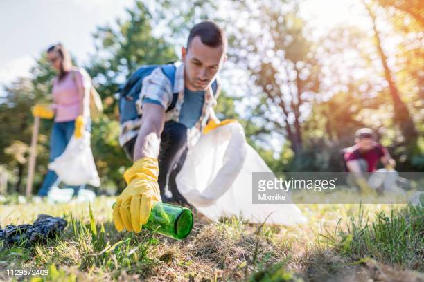 students cleaning the local park from trash - garbage stock pictures, royalty-free photos & images
