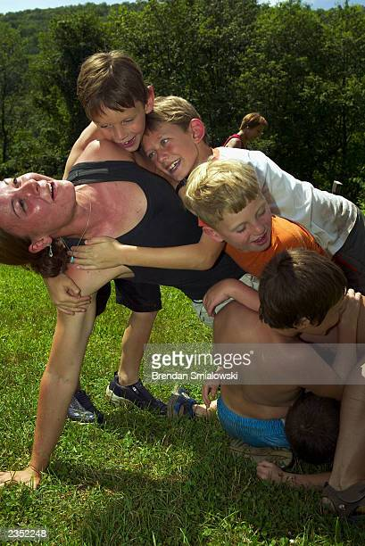 Students climb onto instructor Bryn Werbos during a game of Yoga tag at the Center for Attention and Related Disorders camp at the Great Hollow...