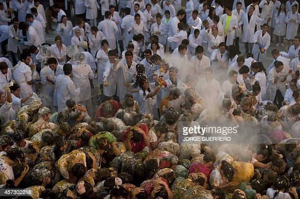 Students cover freshman year medical students with food stuffs during a faculty of medicine hazing at the University of Granada in Granada on October...