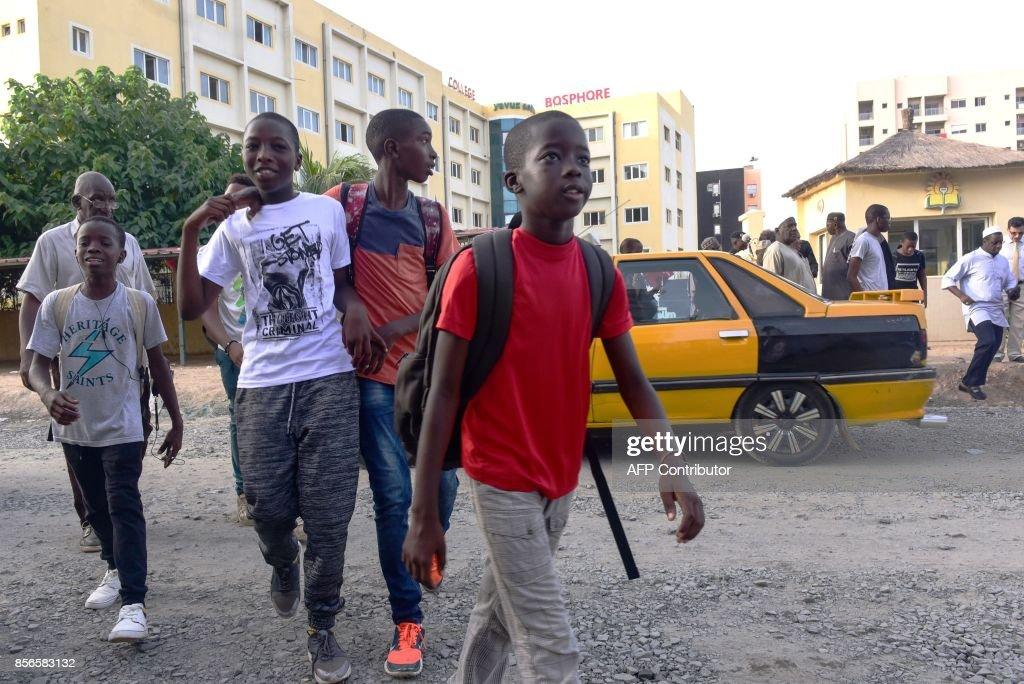 Students cross the street outside the Yavuz Selim school in Dakar on