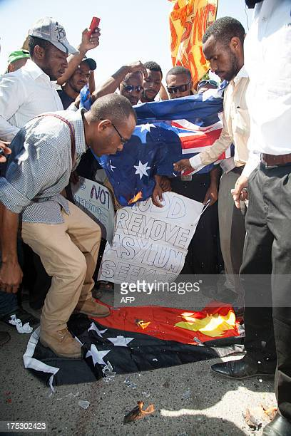Students deface Papua New Guinea and Australia national flags in Port Moresby on August 2 during a protest rally against Australia and PNG's asylum...