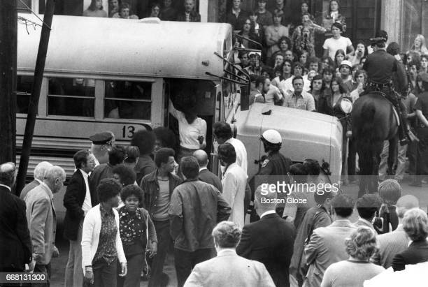 Students disembark from a school bus at South Boston High School as a crowd watches on the first day of federally imposed desegregation Sep 12 1974