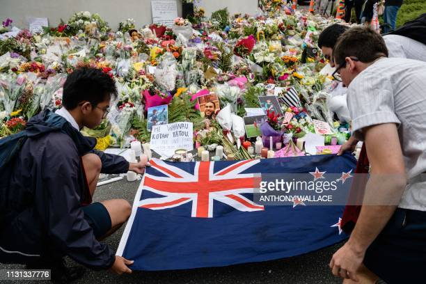 Students display the New Zealand national flag next to flowers during a vigil in Christchurch on March 18 three days after a shooting incident at two...