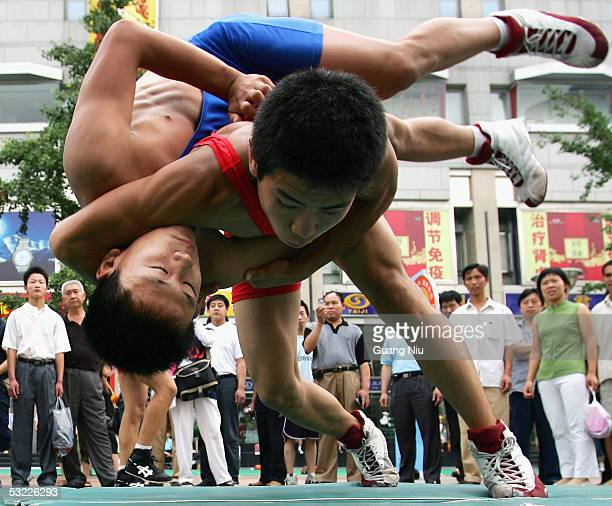 Students display wrestling skills to promote the 2008 Beijing Olympic Games at the downtown business district on June 12 2005 in Beijing China...
