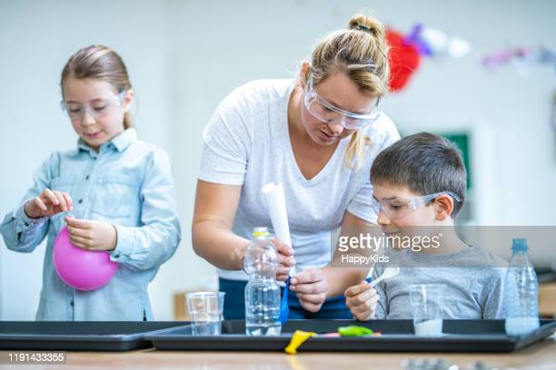 students doing science experiment in laboratory - teacher bending over stock photos and pictures