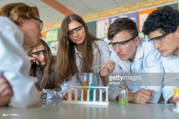 studenten doen wetenschap experiment in laboratorium - scheikunde stockfoto's en -beelden