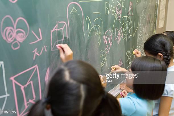 Students doodling on blackboard