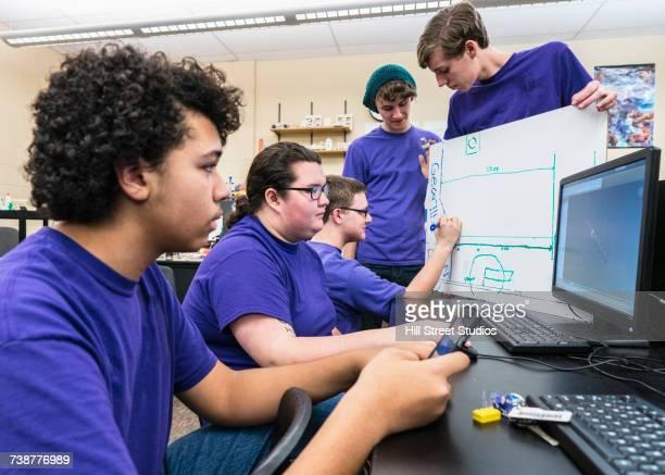 students drawing diagram and using computers at school - cinque persone foto e immagini stock