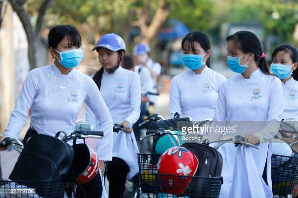 Students dressed in Ao Dai on the way to school Cai Be Vietnam