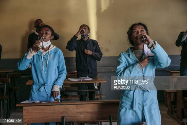 Students drink from bottles of Covid Organics a herbal tea touted by Madagascar President Andry Rajoelina as a powerful remedy against the COVID19...