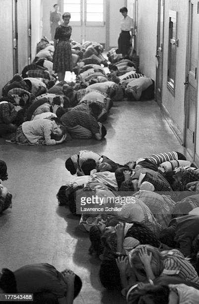 Students 'duck cover' their heads in the hallway of their school during a atomic bomb drill 1960s