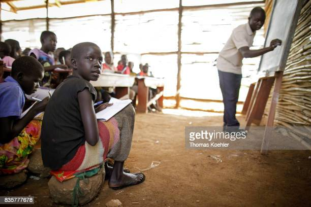 Students during the lessons in a school at the Rhino Refugee Camp Settlement in northern Uganda Here children of local people and refugees are taught...