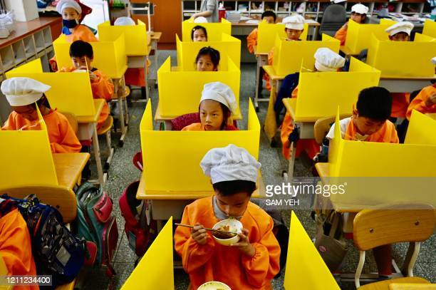 TOPSHOT Students eat their lunch on desks with plastic partitions as a preventive measure to curb the spread of the COVID19 coronavirus at Dajia...