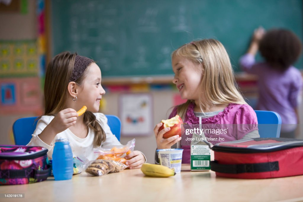 Students eating lunch in classroom : Stock Photo