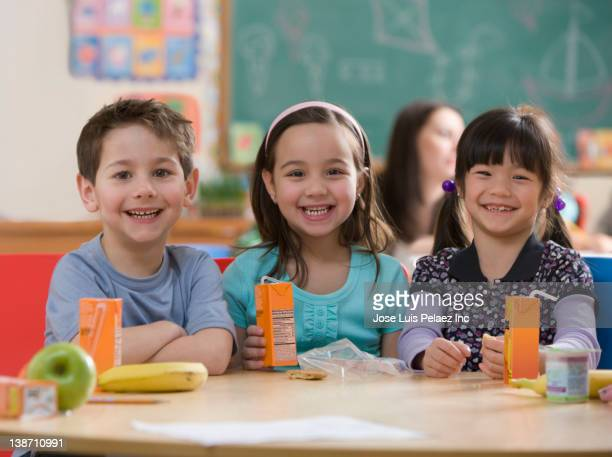 students eating lunch together in classroom - juice carton stock photos and pictures