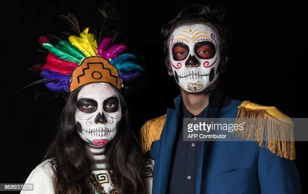 Students Edith Galilea Isidro and Josafat Hernandez pose for a photograph disguised as Catrina during a Catrinas competition at the University of...