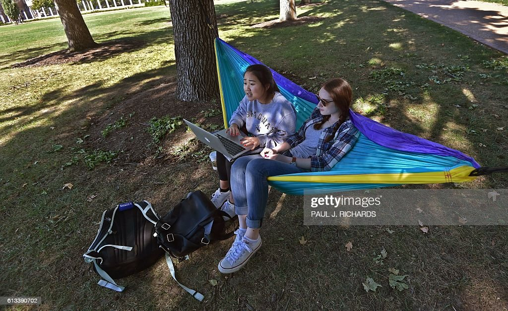 Students Elizabeth (L) and Marni study outside the site of the second US Presidential debate on October 8, 2016, at Washington University in St. Louis, Missouri. US Presidential Republican nominees Donald Trump and Democrat nominee Hillary Clinton will debate for the second time in St. Louis on October 9. / AFP / PAUL