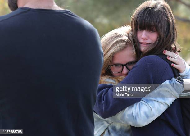 Students embrace at a nearby park after being evacuated from Saugus High School after a shooting at the school left two students dead and three...
