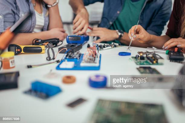 Students engineers working on a computer part