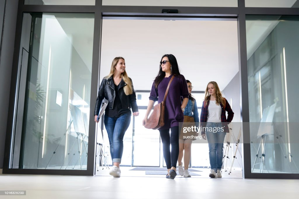 students entering college building by glass doors ストックフォト