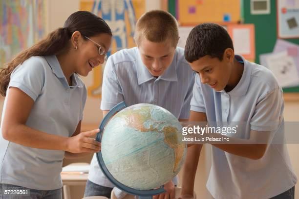 Students examining globe