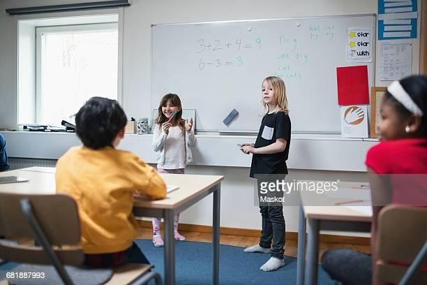 Students explaining to classmates in classroom