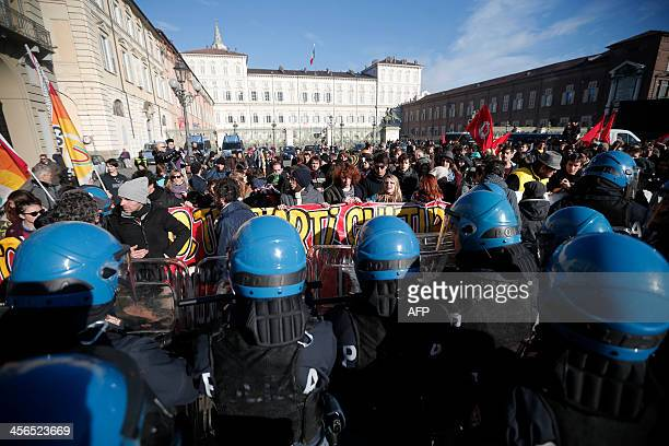 Students face riot police during a protest against the local government in downtown Turin on December 14, 2013. Protesters clashed with police during...