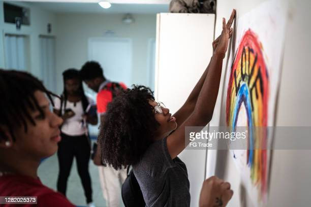 students fixing in the wall a poster about lgbtqi rights - students' union stock pictures, royalty-free photos & images